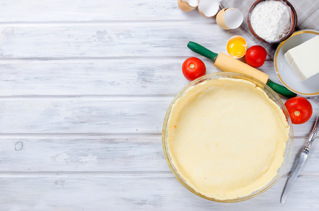 raw base of dough for baking in a baking dish and ingredients for greek pie with cheese and tomatoes, copy space, top view