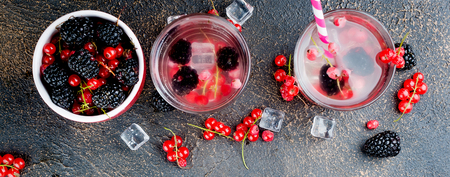 two glasses with a cocktail of red currant, blackberry and ice and berries in bowl on a dark background, copy space