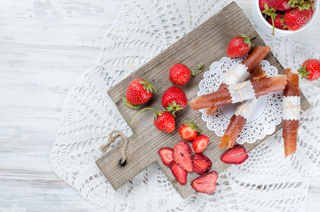 ripe juicy strawberries in the form of dry chips and fruit leather rolls on white wooden table. Detox concept. Healthy food, Fruits amazing candy.