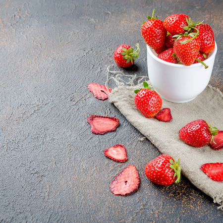 ripe juicy strawberries in the form of dry chips and fruit leather rolls on dark background. Detox concept. Healthy food, Fruits amazing candy. Reklamní fotografie