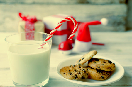 A glass of milk with candy and cookies with chocolate chip  for Santa on christmas eve on white wooden table. Christmas lcard. toned photo