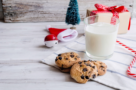An empty glass of milk with candy and cookies with chocolate chip for Santa on christmas eve on white wooden table. Christmas card. Stockfoto