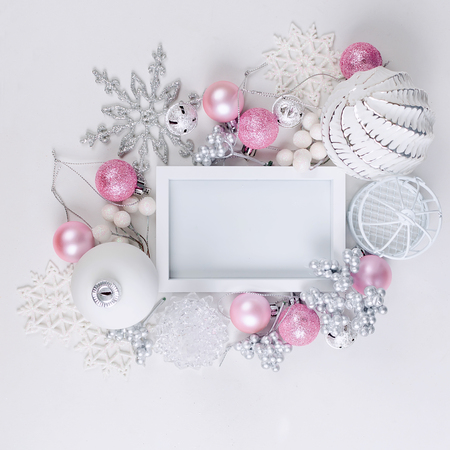 Christmas greeting card with empty white frame, pink and white holiday decoration, ball and toys on a white background, copy space