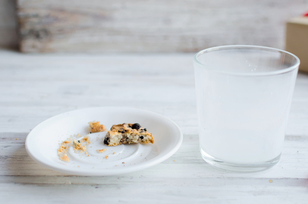 An empty glass of milk with candy and cookies with chocolate chip for Santa on christmas eve on white wooden table. Christmas card. Stock Photo