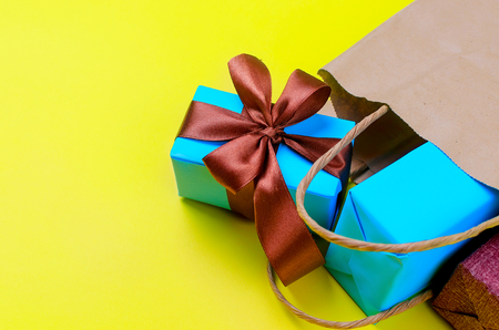 blue gift boxes decorated with a brown bow fall out of the crafting bag lie on a yellow background Stockfoto - 114216480