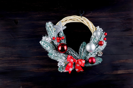 Making craft xmas wreath . Christmas handmade diy background, fir branches, cones, bells, balls.. Top view on dark wooden table