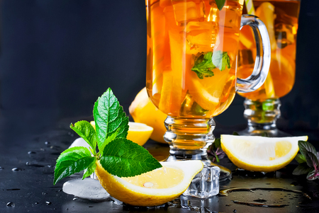 lemon slices and mint leaves, ingredients for tea close-up on a black background, copy space Stock Photo