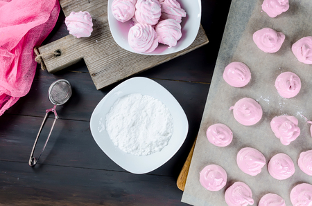 making homemade cherry marshmallow, sprinkles in icing sugar, on a dark background, a series of photos  copy space, Stock Photo