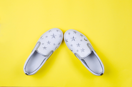 Women or teenage fashion, white slipons, Stylish shoes on yellow background. Beauty and fashion concept. Flat lay, Top view copy space.