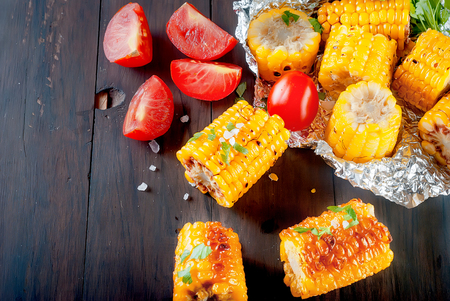 Tasty grilled corn cobs on the foil with solt, herb, spices, butter and tomatoes on dark wooden table, close up Stock fotó