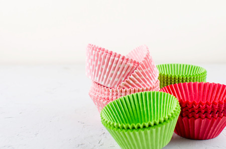 Colorful Bright green, pink and red colored paper baking cups for cupcakes or muffins on light grey concrete background, copy space