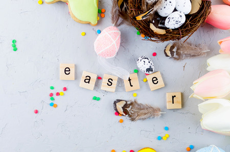 small decorative nest with eggs, Easter gingerbread cookies, buoquet tulips and the inscription Easter in wooden letters on grey concrete background, Easter greeting card,