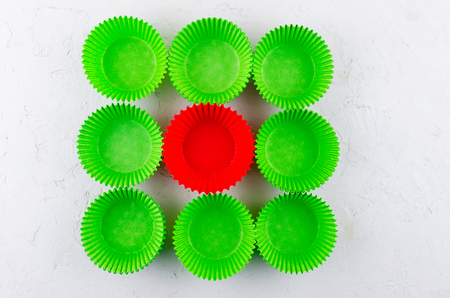 Brightly green and red colored paper baking cups for cupcakes or muffins on light grey conkrete background, copy space