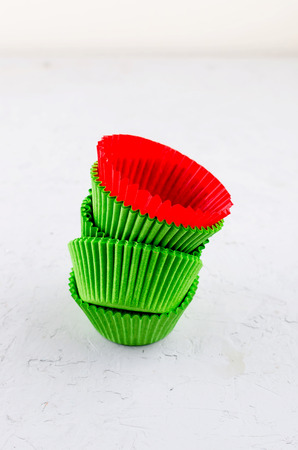 Brightly green and red colored paper baking cups for cupcakes or muffins on light grey conkrete background, copy space 免版税图像