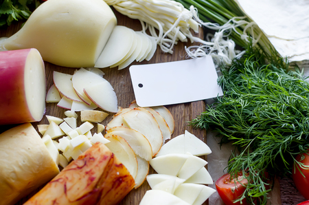 Assorted homemade cheeses in various shapes and sizes on the wooden background, suluguni, pigtail, Cacocavallo with tomatoes and herb and empty blank for the logo of a home cheese factory Imagens - 121182238