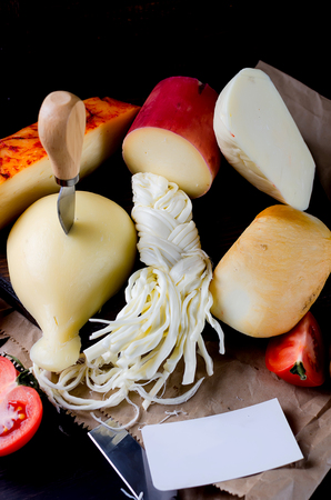 Assorted homemade cheeses in various shapes and sizes on the wooden background, suluguni, pigtail, Cacocavallo with tomatoes and herb and empty blank for the logo of a home cheese factory