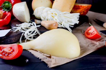 Assorted homemade cheeses in various shapes and sizes on the wooden background, suluguni, pigtail, Cacocavallo with tomatoes and herb