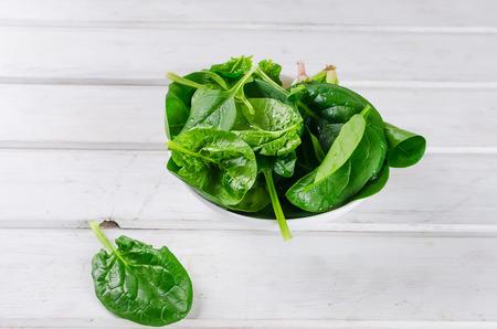 foglie di spinaci verdi crudi in una ciotola bianca su un vecchio tavolo bianco rustico in legno, spazio copia Archivio Fotografico