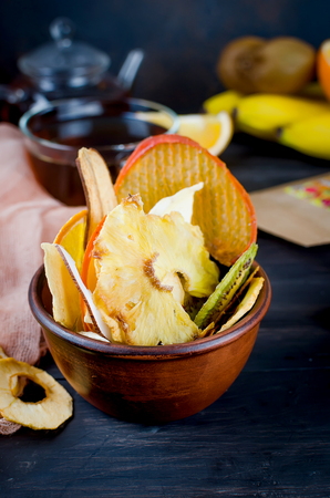 Many variety Fruit chips laid in bowl on dark old wooden background , concept of healthy and proper nutrition, snack, top view, copy space