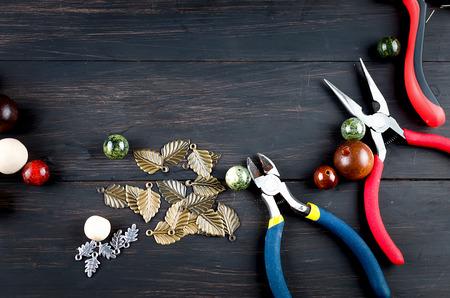 Herramientas para joyería artesanal. Cuentas de madera, alicates y accesorios para crear joyas de moda hechas a mano en la mesa de madera oscura Vista superior