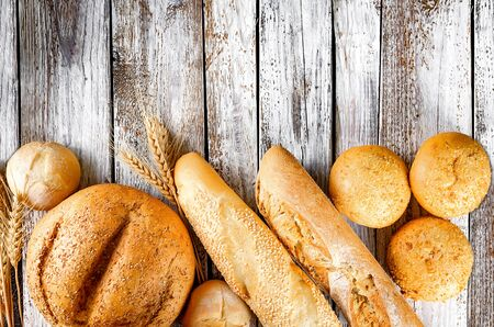 assortment of different types of bread, loaf, baguettes, loaves, rolls with ears of wheat on old white wooden table in low key, healthy concept Stock Photo