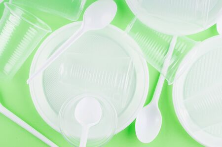 White Disposable cups, plates, forks, knives on light green background close-up - Environmental problem concept, copy space