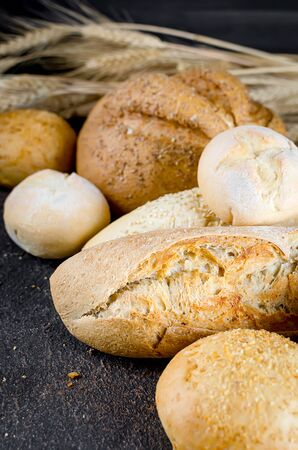 assortment of different types of bread, loaf, baguettes, loaves, rolls with ears of wheat on black background.