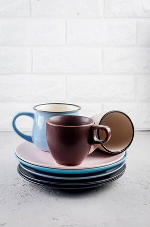 Set of clean Ceramic crockery tableware on gray concrete background, color bowls, plate, cup, dishes. tableware set concept