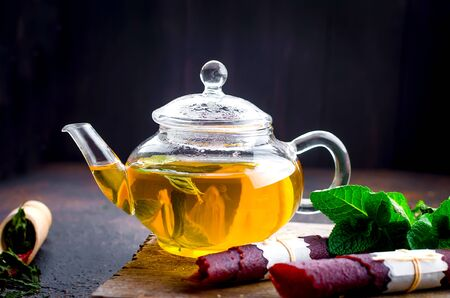 Hot herbal tea in a tea pot, leaves fresh mint, dry fruits leather roll and dry mint leaves with strawberry in a wooden spoon on wooden background, copy space