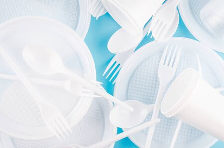 White Disposable cups, plates, forks, knives on light green blue background close-up - Environmental problem concept, copy space