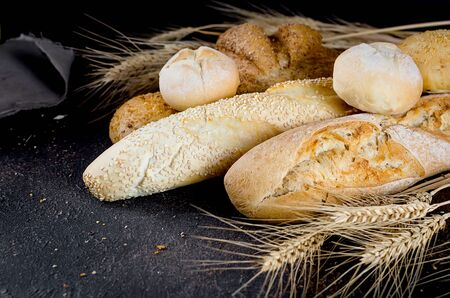 assortment of different types of bread, loaf, baguettes, loaves, rolls with ears of wheat on black background, healthy concept, copy spase, bakery products Stock Photo