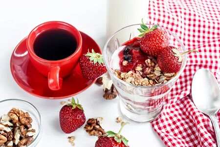 Homemade baked granola with Yogurt  and strawberries in small glass and cup of black coffe for breackfast on rustic wooden table