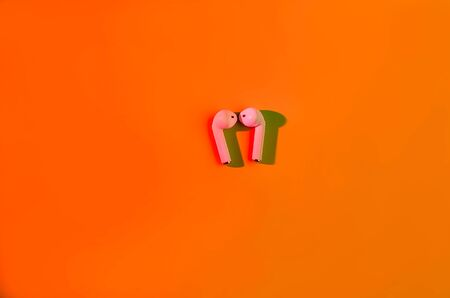 New Ear pods wireless entangled 3.5 headphones into the open charging case for smartphone in trendy neon red light on green background. L Copy Space Zaporizhia, Ukraine, July 07 2019, Reklamní fotografie