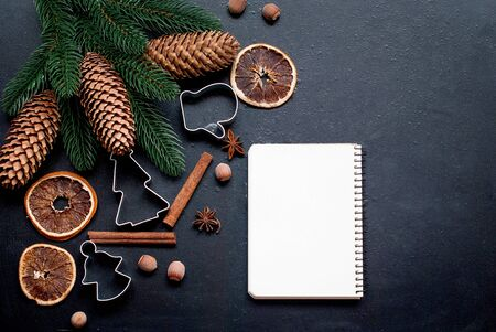 dry Orange, cookie molds, cinnamon sticks, nuts, comes and fir brunches on black background with empty blank for text, Baking concept background with cookbook, ingredients for Christmas cookies