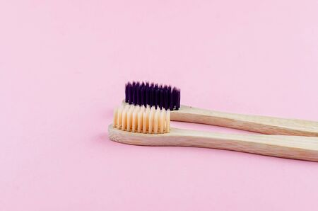 two wooden eco brushes with natural bristles on pink paper background. Plastic free set. Zero waste, eco friendly concept.