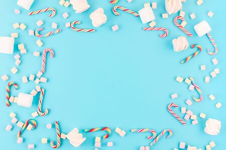 Christmas or New Year background. Candy caramel cane and marshmallow on pastel blue background. Christmas holiday concept. Flat lay, top view, copy space