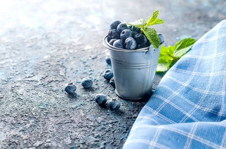 ripe  blueberries in mini bucket with leaves mint on a dark concrete background Banque d'images