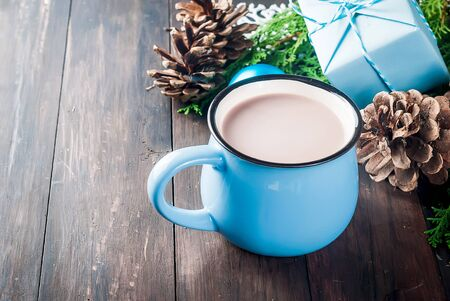 Hot cocoa in blue cup on dark wooden table with Christmas decor, giftes, pine cones, wrapping craft paper .  Making xmas gifts  Top view, copy space. winter Holiday Concept.