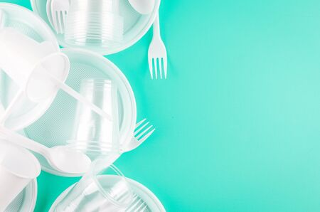 White Disposable cups, plates, forks, knives on light blue background close-up - Environmental problem concept Zdjęcie Seryjne
