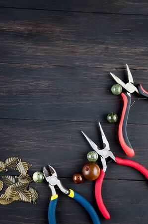 Tools for handmade jewelry. wooden Beads, plier and accessories to create hand made fashion jewelry on dark wooden table Top view 写真素材
