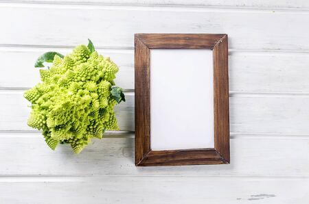 Fresh green romanesco, Raw Organic Cabbage Ready for Cooking on a cutting board on white wooden background