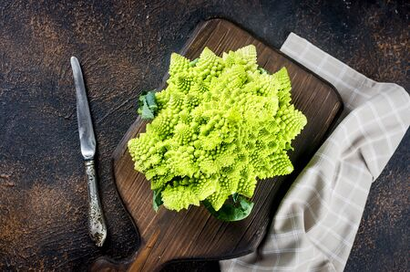 Fresh green romanesco, Raw Organic Cabbage Ready for Cooking on a cutting board on dark wooden background