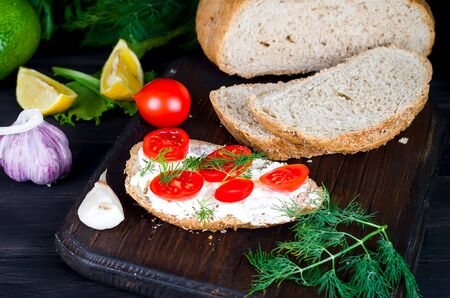 rye bread sandwiches with soft mozzarella or feta cheese and tomatoes on a dark rustic table from old boards