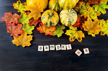 Autumn background with decorative pumpkins, leaves and text pumpkins on a wooden table.