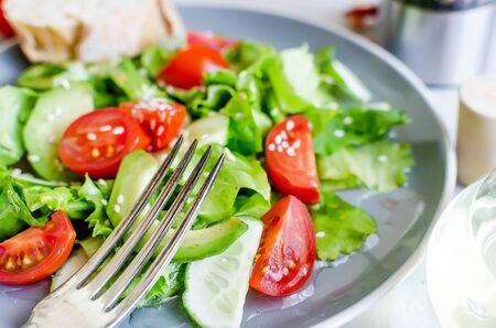 Ensalada orgánica verde fresca con ingredientes crudos de cerca. Sabrosa ensalada con lechuga, tomates cherry, pepinos, verduras y cebollas en placa gris para el almuerzo, vista superior. Alimentación saludable, concepto de dieta