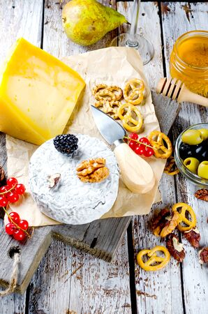 Different kinds of Delicious cheeses on a wooden board and many snack, nuts, honey, berries, olives on a white old wooden table. Food ingredients background. Selective focus.