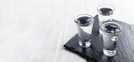 three Vodka shots with ice on black stone board on white wooden table, copy space, Banner, Template mockup greeting card with place for text,