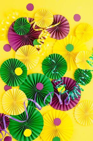 Confettis en papier coloré, masque de carnaval et serpentine colorée sur fond jaune avec espace de copie, carte de voeux et modèle d'invitation à la fête pour le carnaval ou l'anniversaire, Mardi Gras,