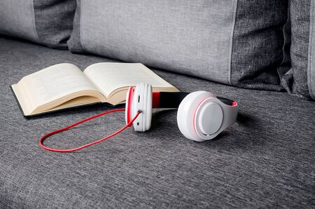 open book with headphones on gray sofa. Audio book concept. modern education, reading. Listening to audiobooks, podcasts, and online courses.  Standard-Bild