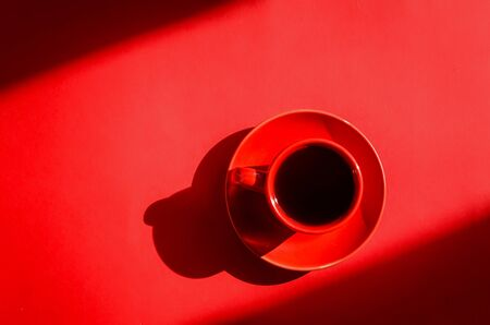 Red cup of coffee with shadows on red background in natural sunlight . Minimalist creative art composition. Conceptual image.  Simple visual concept. 版權商用圖片